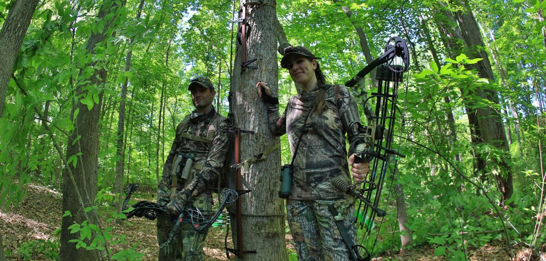 man and woman bowhunting